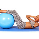 African Woman doing crunches with legs on swiss ball