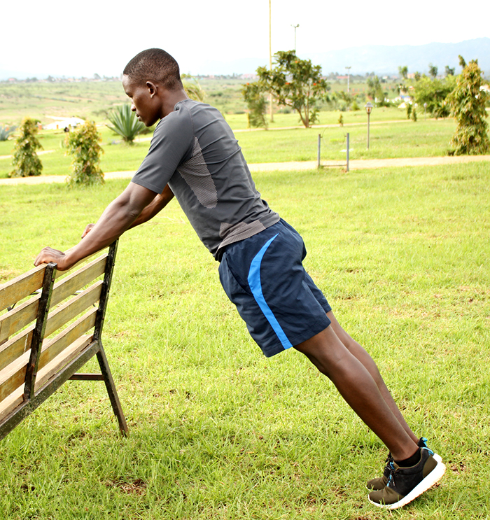 Athletic Male Doing Incline Push Ups on A Bench Outdoors