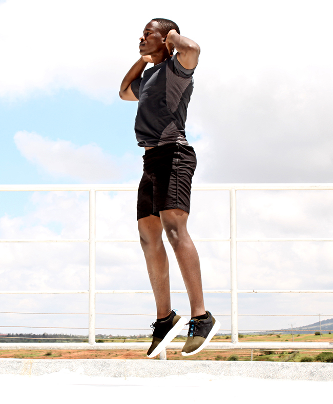 Athletic Man Doing Jump Squats With Hands on Head