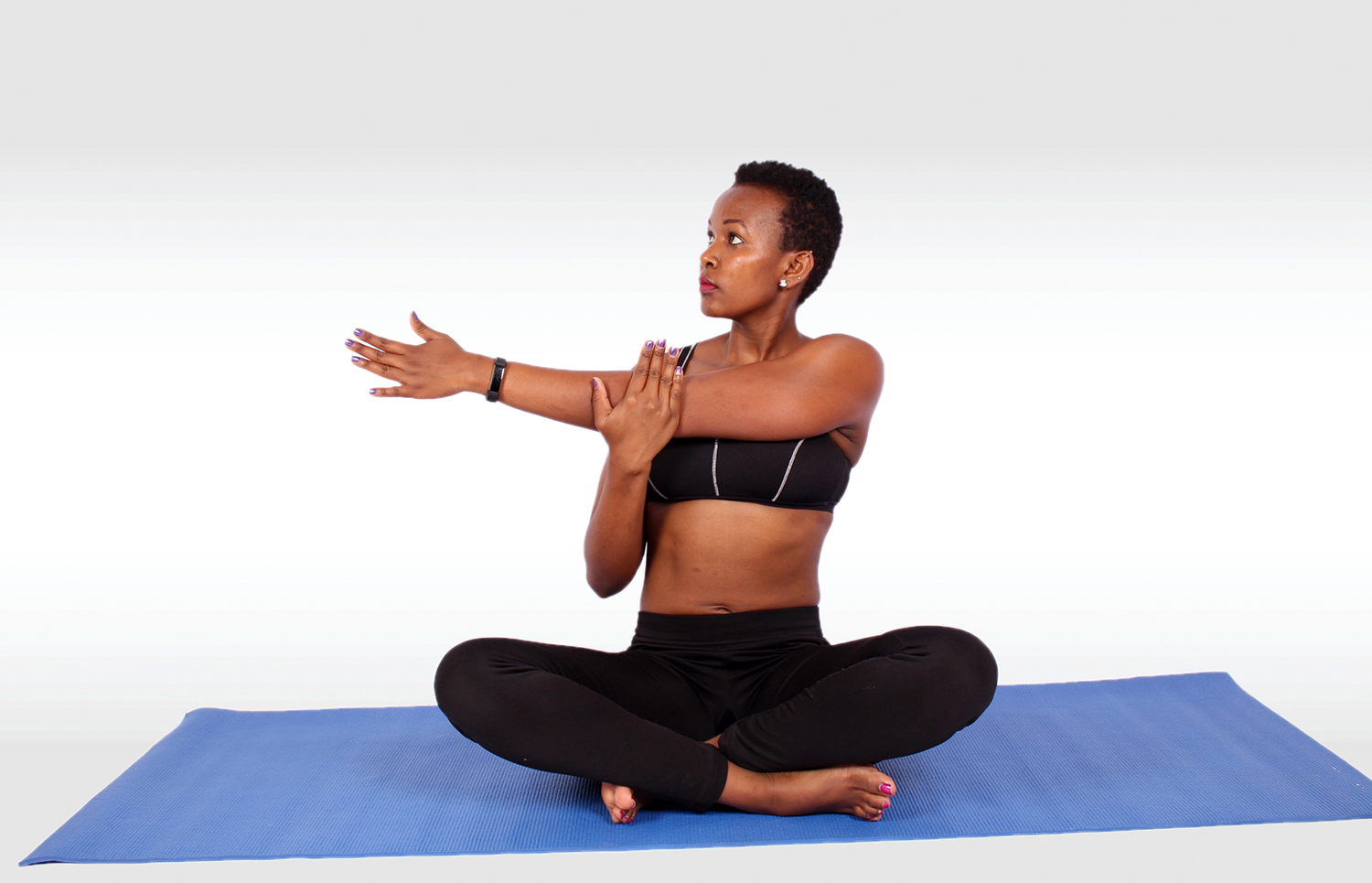 Young Sporty Woman Stretching Shoulder While Sitting in Yoga Pose