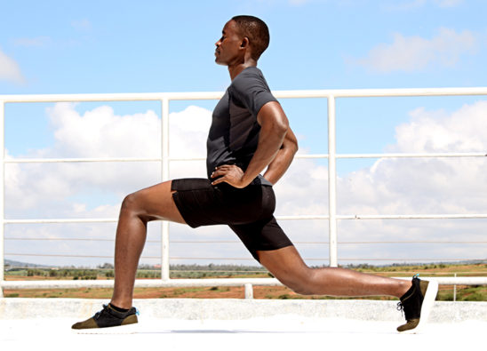 Exercising Young Man Doing Lunges With Hands on Hips