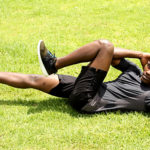 Fit Man Doing Ab Bicycle Crunches on Grass