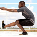 Fit Man Doing Pistol Squat on One Leg Outdoors