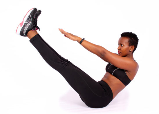 Fit african woman doing v ups ab exercise