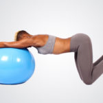Fit woman stretching and exercising with swiss ball