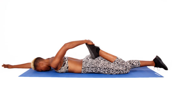 Fitness Woman Stretching Leg Lying on Face-down on Yoga Mat