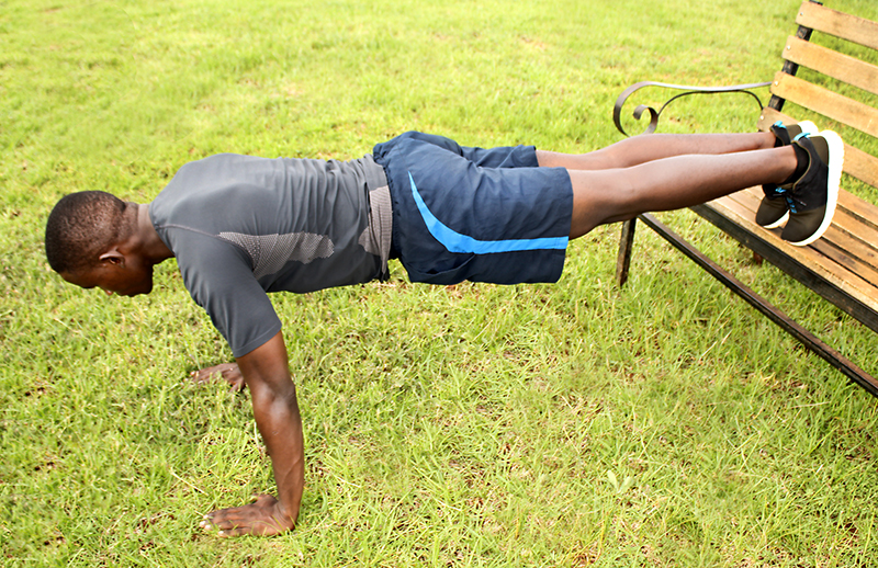 Fitness Man Doing Decline Push Ups With Legs Raised on a Bench