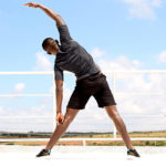 Fitness Man Doing Standing Side Stretch Outdoors