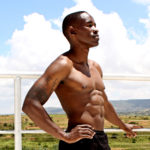Fitness Man With Abs Standing Outdoors on Sunny Day