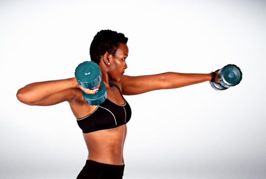 Fitness Woman Lifting Dumbbells To Build Arm and Shoulder Muscles