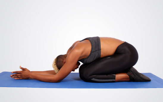 Fitness Trainer Practicing Yoga Sitting in Child Pose Exercise