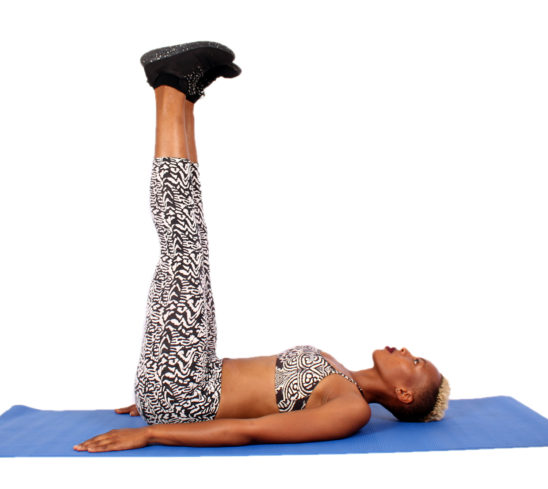 African Woman Doing Leg Raises Lying on Yoga Mat