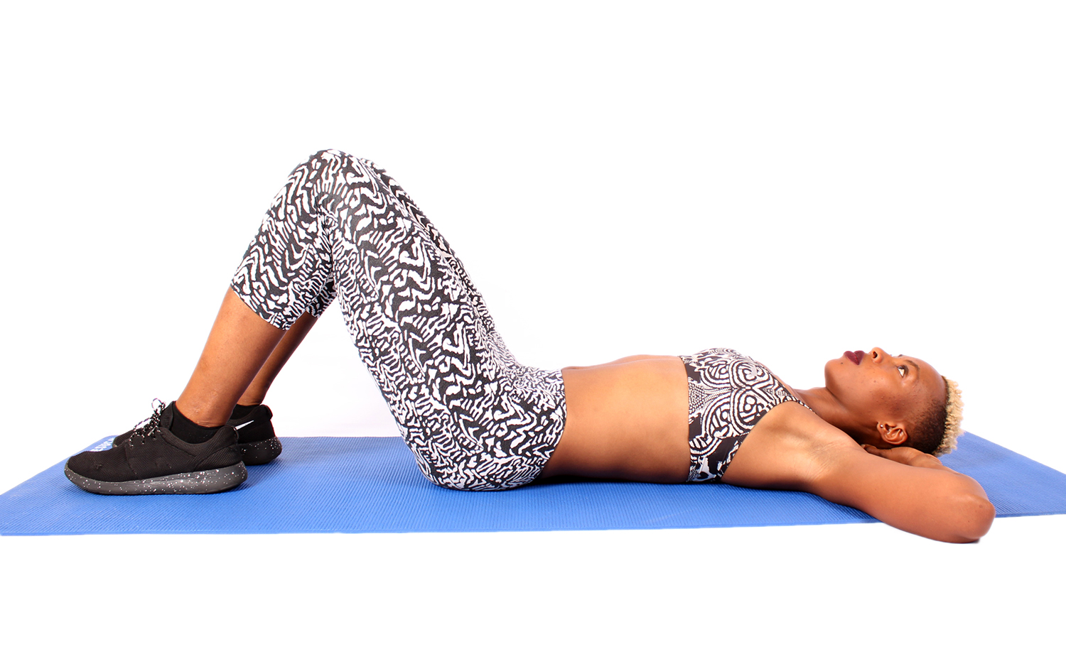 Fitness Woman Lying on Yoga Mat With Knees Bent