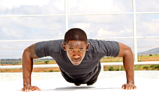 Front View of African Man Doing Push Ups Outdoors