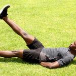 Healthy Man Lying on Grass Doing Ab Exercise Flutter Kicks