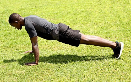 Man Doing Push Ups Outdoors on Grass