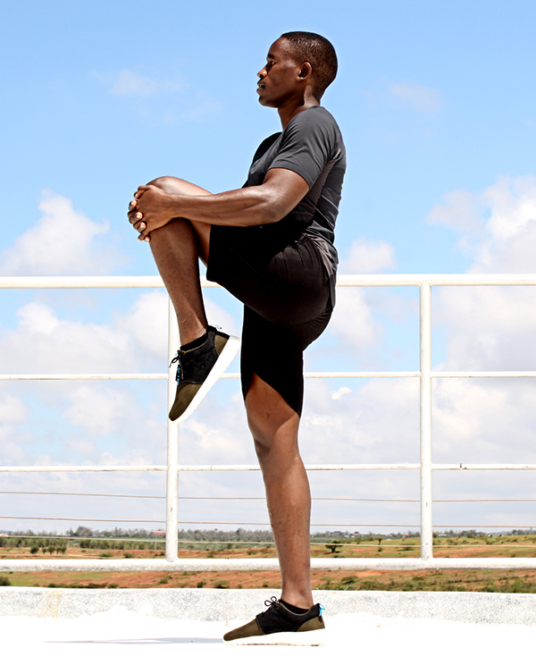Man Doing Standing Hamstring and Glutes Stretches Before Running. Knee to Chest Stretch