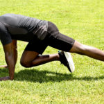 Man Shows How to Do Mountain Climbers Exercise on Grass