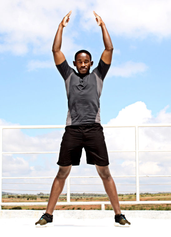 Muscular Athlete Doing Jumping Jacks Outdoors