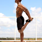Shirtless Fit Man Stretching Legs After Workout