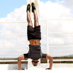 Strong Black Man Doing Handstand Push Ups Outdoors