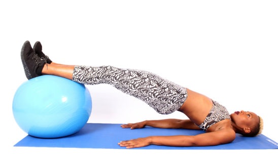 Woman Exercising With Hips Raised Using a Swiss Ball