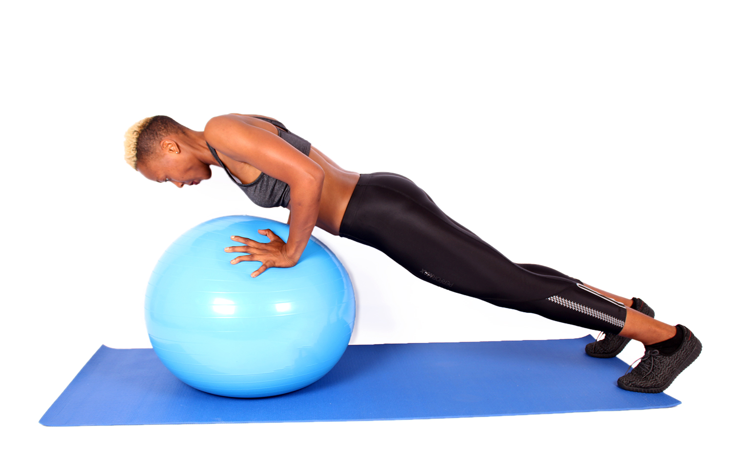 Strong woman doing push ups on swiss ball fitball