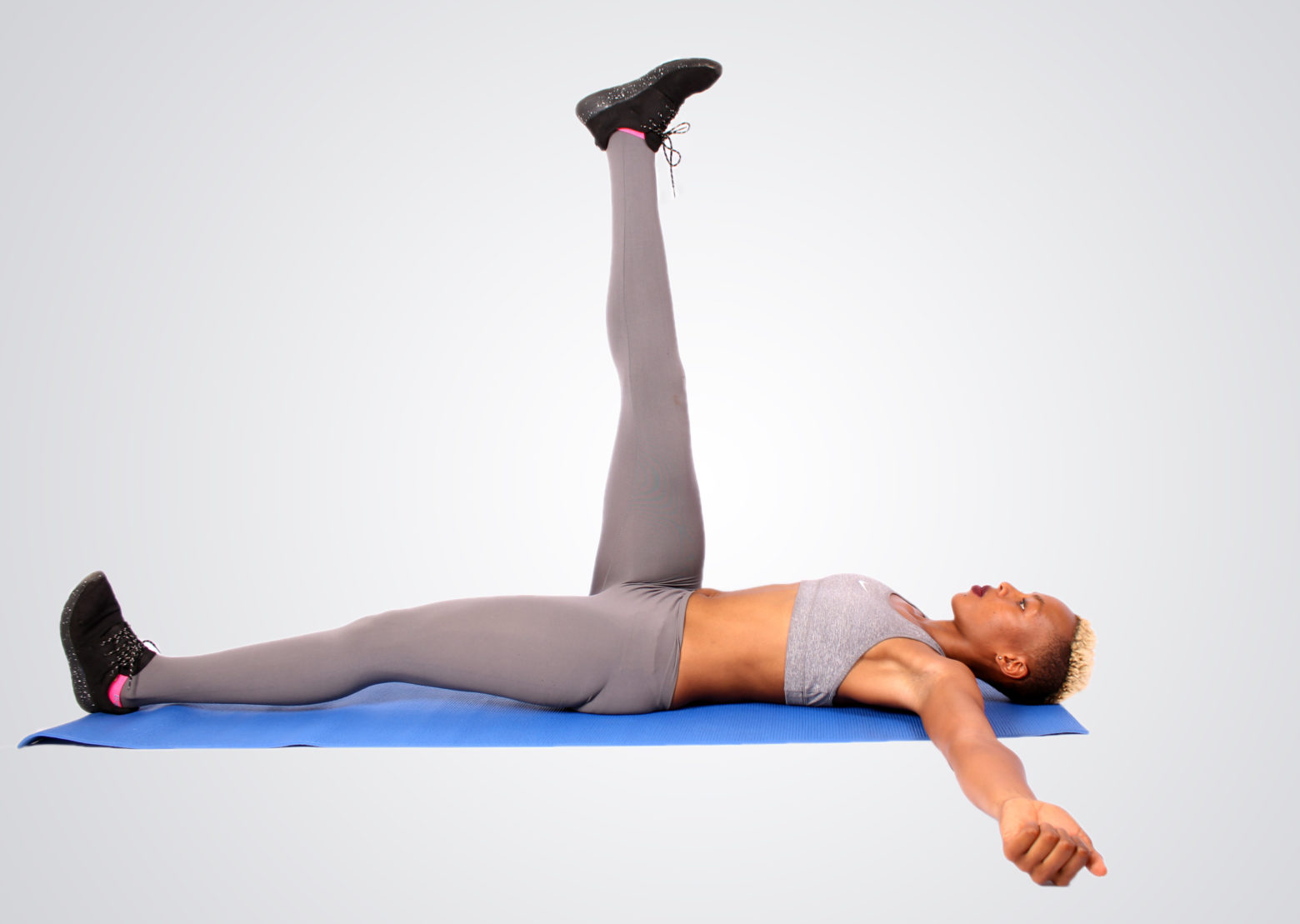 Healthy Woman Exercising Lying on Her Back With One Leg Raises