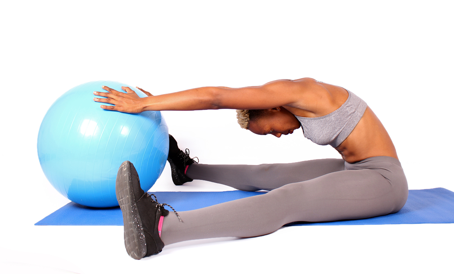 Woman Doing Pilates Exercise With Swiss Ball