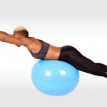 Fit Woman Doing Back Extensions Exercise on Swiss Ball