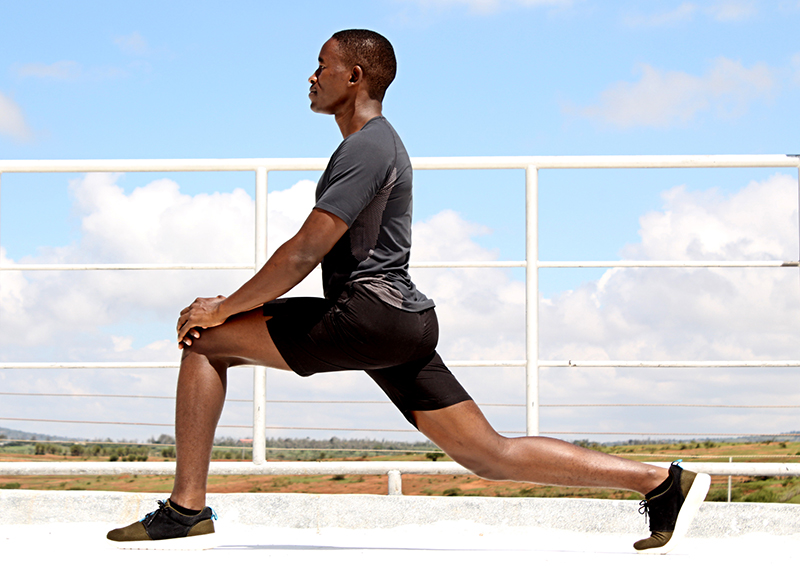 Young Fit Man Stretching Outside in Forward Lunge Position