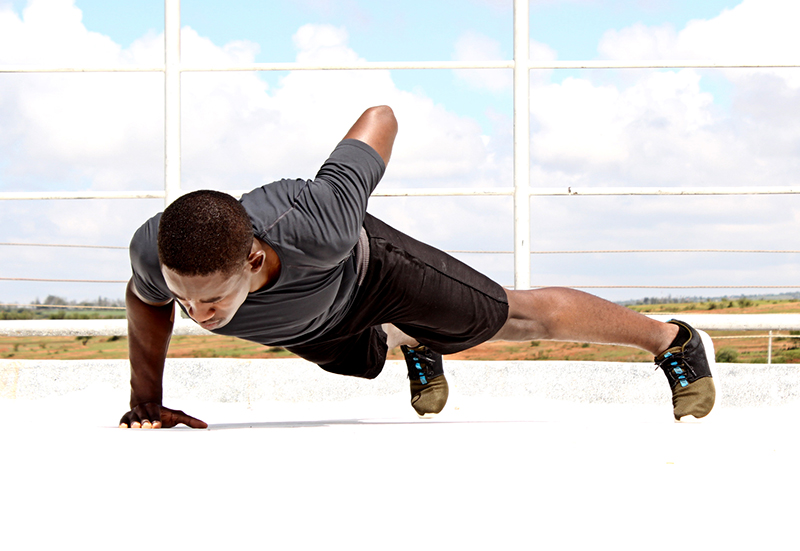 Young Fitness Man Doing One Arm Push Ups Outdoors