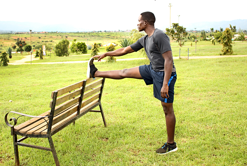 Young Man Stretching Legs on A Bench in the Park Before Running