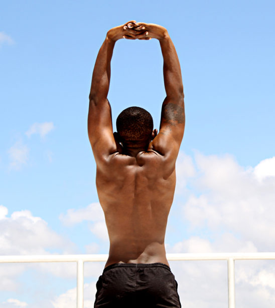 Young Muscular Man Stretches Body From Behind