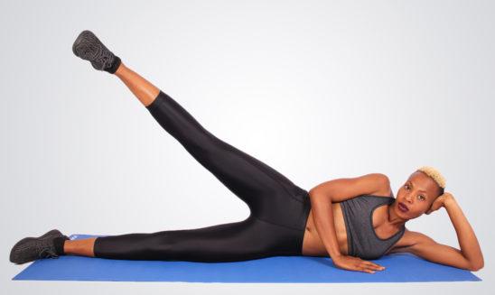 African Woman Doing Lying Side Leg Raises on Yoga Mat