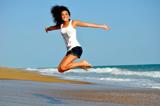 Fitness Woman Jumping At The Beach