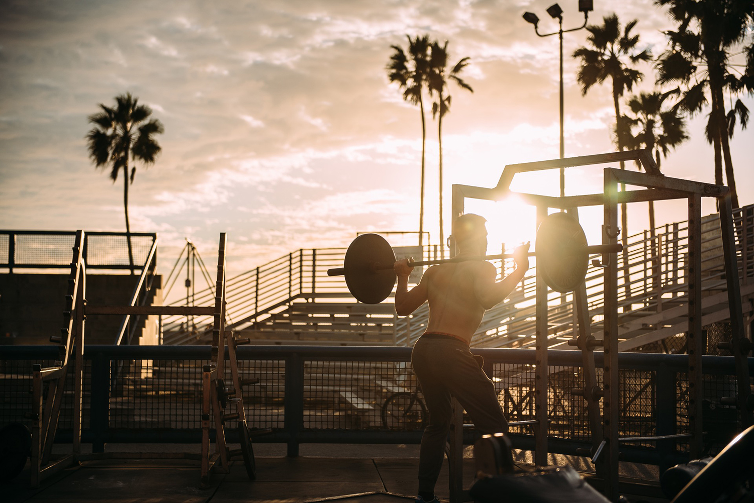 Fitness Man Doing Barbell Squats Outside