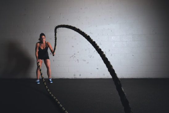 Fitness Woman Exercising With Battle Ropes