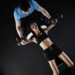 Trainer Helping Woman Perform Dumbbell Bench Press