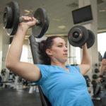 Strong Woman Doing Shoulder Press Exercise Using Dumbbells