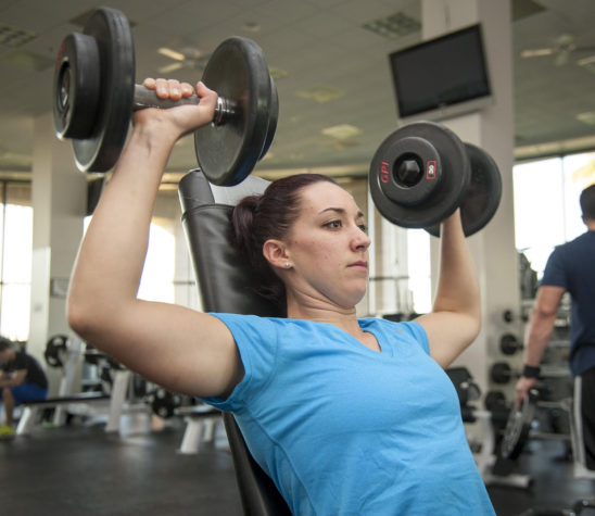 Strong Woman Doing Shoulder Press Exercise Using Dumbbells