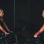 Fitness Woman With Dumbbells Using The Mirror In The Gym