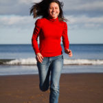 Smiling Woman Running at The Beach