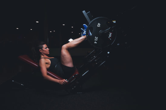 Fit Woman Doing Leg Press Exercise In The Gym