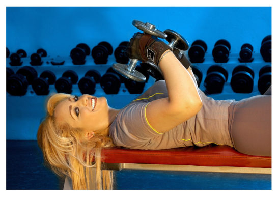 Smiling Woman Lying on Bench Lifting Dumbbells