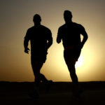 Silhouettes of Two Men Running Outdoors in The Evening