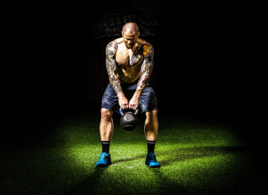Athletic Man Exercising With Kettlebells