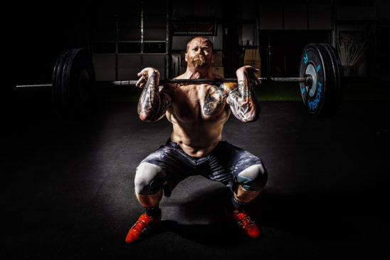 Strong Man With Tattoos Doing Front Barbell Squat Exercise
