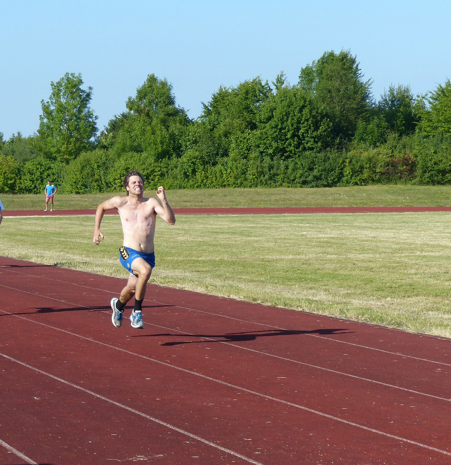 Fitness Man Sprinting on The Field Track