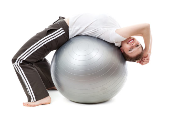 Fit Woman Stretching and Exercising on Swiss Ball